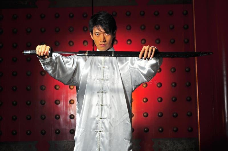 Uomo asiatico Unsheading una spada fotografia stock