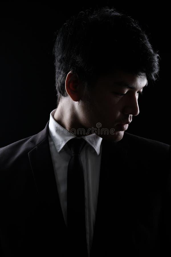 Uomo asiatico in vestito convenzionale nero nello scuro fotografie stock