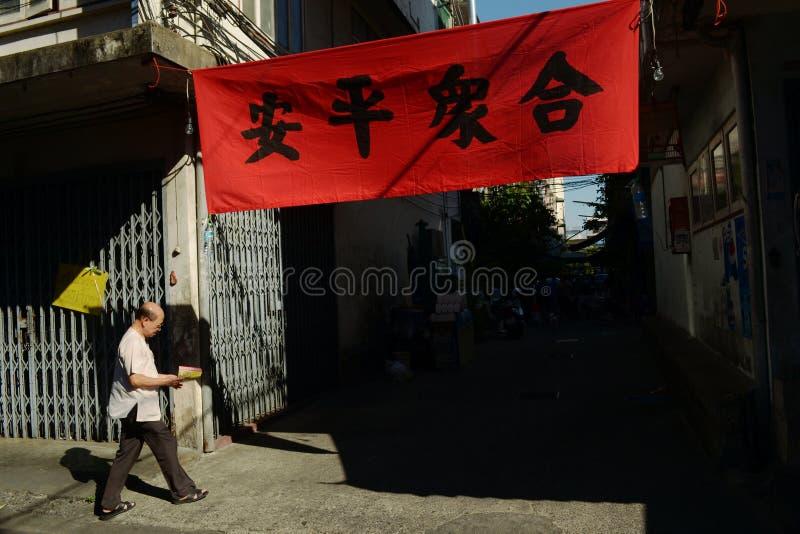 Uomo asiatico vicino al manifesto rosso con i geroglifici cinesi immagine stock libera da diritti