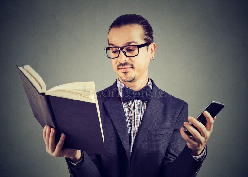 Uomo astuto con il libro di lettura del telefono immagine stock libera da diritti