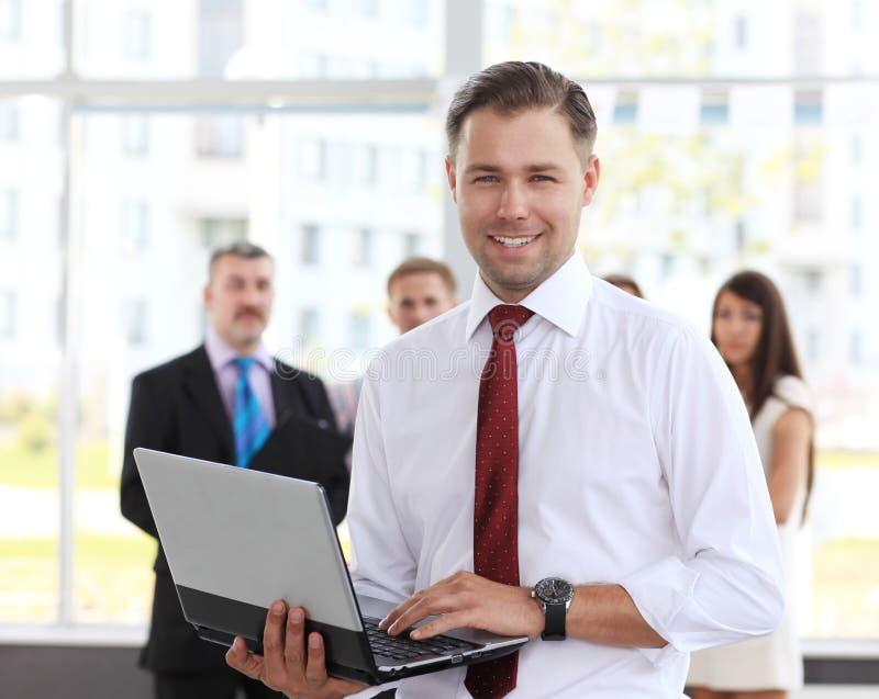 Uomo astuto di affari che per mezzo del computer portatile fotografia stock