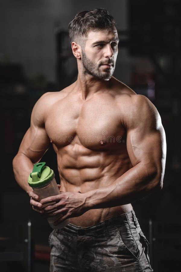 Uomo atletico bello di forma fisica che tiene un agitatore e che posa palestra immagine stock libera da diritti