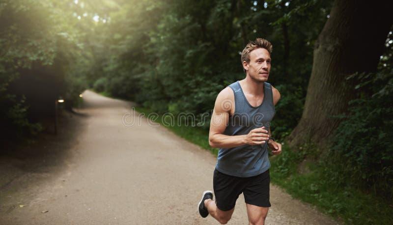 Uomo atletico che fa esercizio corrente al parco fotografia stock libera da diritti