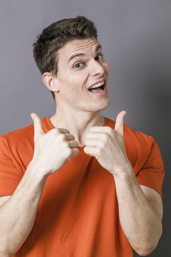 Uomo atletico emozionante con i pollici su per dinamismo sportivo immagini stock