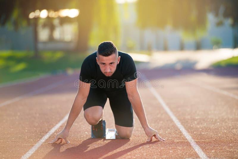 Uomo atletico sulla pista che inizia a funzionare Concetto sano di forma fisica con lo stile di vita attivo fotografie stock