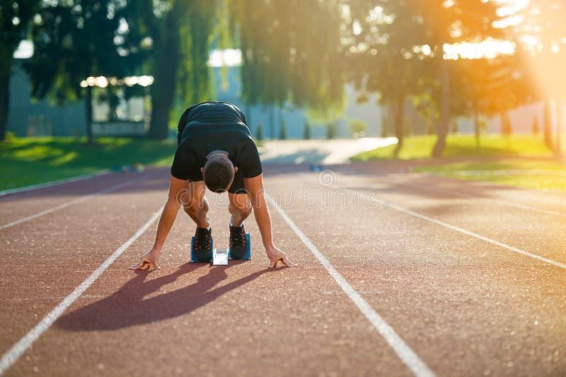 Uomo atletico sulla pista che inizia a funzionare Concetto sano di forma fisica con lo stile di vita attivo immagine stock libera da diritti