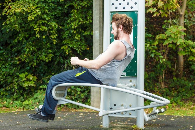 Uomo attivo che si esercita sul banco all'aperto fotografie stock libere da diritti