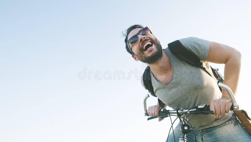 Uomo attivo di sport con l'espressione emozionante del fronte che esplora e che viaggia in mountain bike sulla strada Stile d'ann fotografie stock libere da diritti