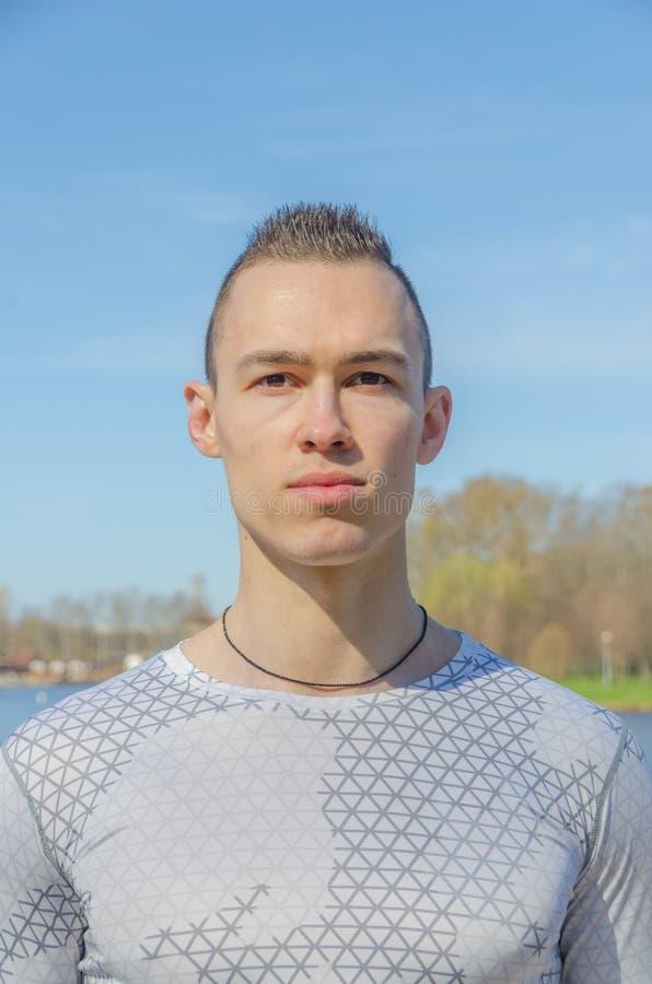 Uomo attraente in abiti sportivi bianchi, primo piano immagine stock libera da diritti