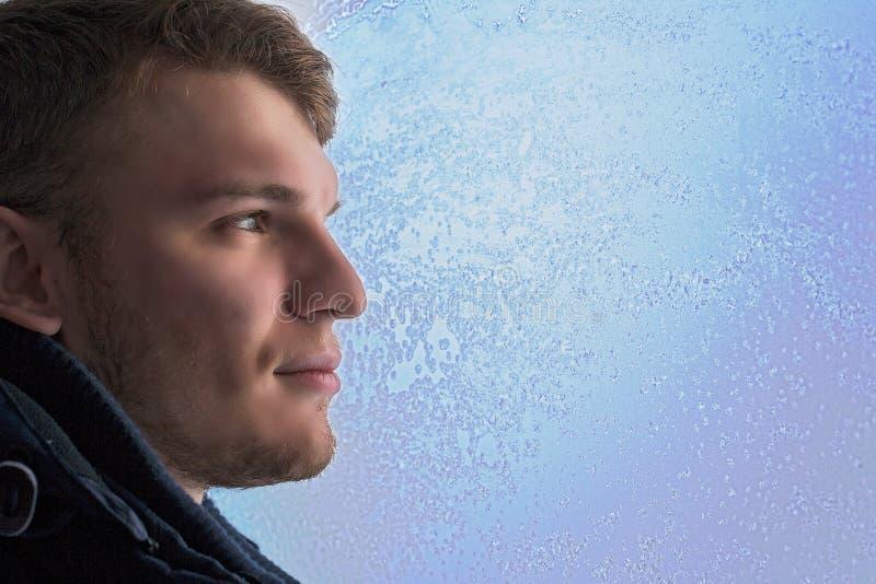 Uomo attraente bianco nella fine di profilo - su contro la finestra nel tema di inverno del gelo fotografia stock
