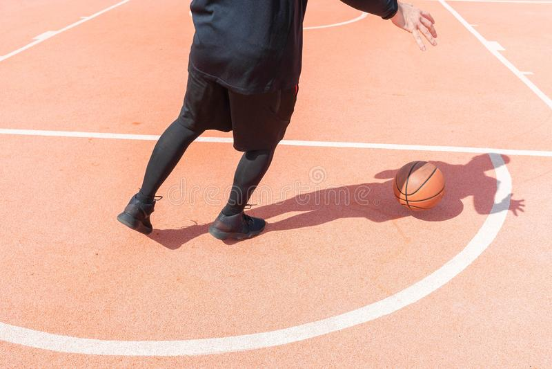 Uomo attraente che gioca pallacanestro sul campo da pallacanestro con la sua ombra fotografie stock libere da diritti