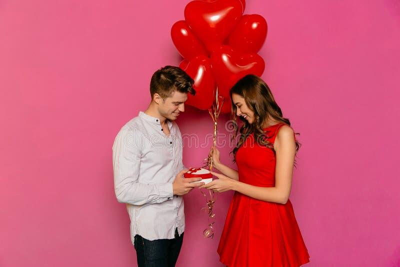 Uomo attraente che rende presente per la sua amica graziosa il giorno del ` s del biglietto di S. Valentino della st immagini stock