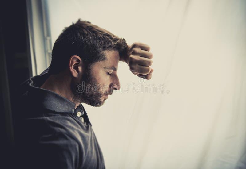 Uomo attraente che si appoggia finestra che soffre crisi e depressione emozionali fotografia stock
