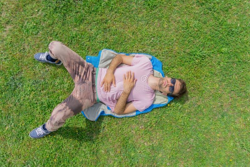 Uomo attraente con gli occhiali da sole che si rilassano sull'erba Disposizione piana fotografia stock libera da diritti
