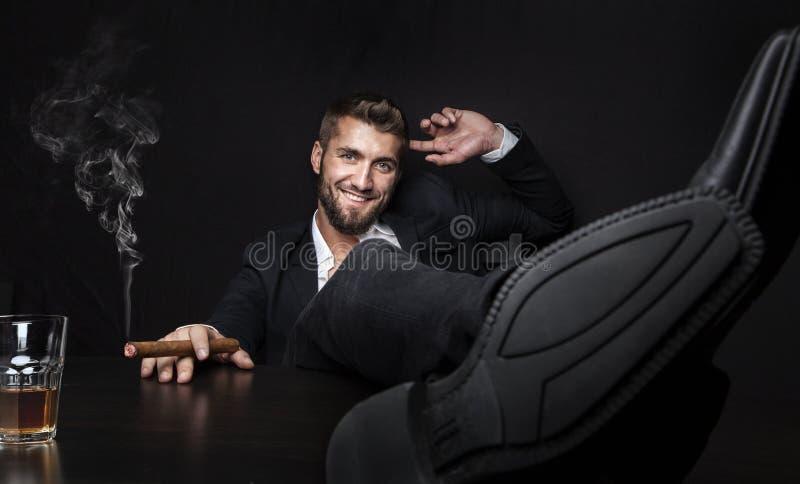 Uomo attraente di affari con il sigaro e una bevanda fotografie stock libere da diritti