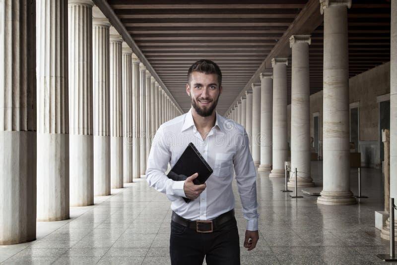 Uomo attraente di affari con un taccuino in sua mano fotografia stock