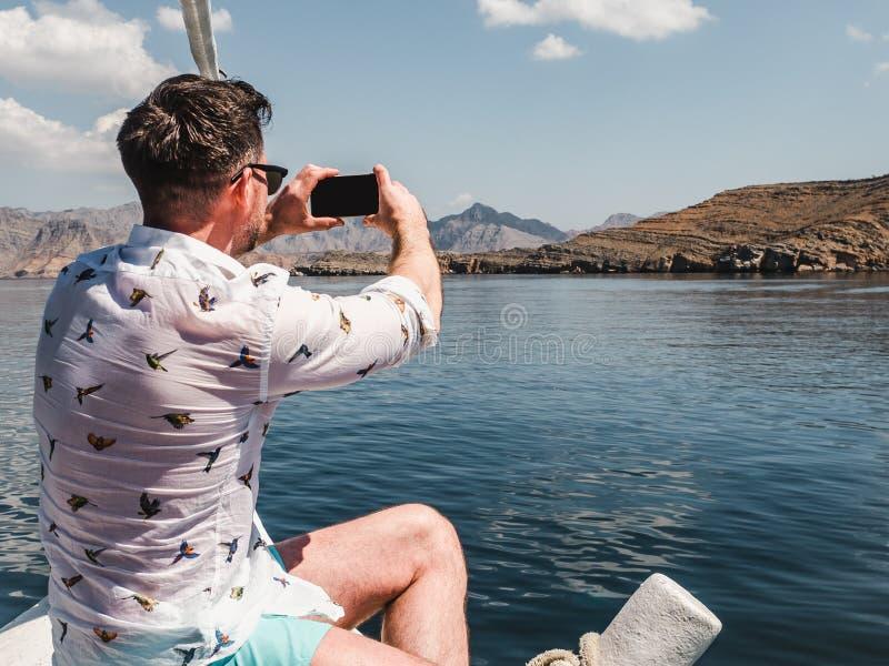 Uomo attraente e alla moda che si siede su una barca immagini stock