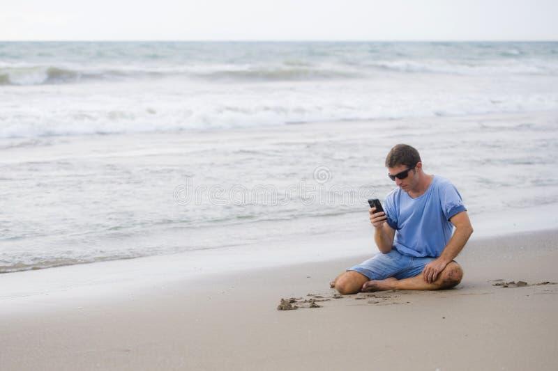 Uomo attraente e bello sul suo 30s che si siede sulla sabbia rilassata sulla spiaggia che ride davanti al mare che manda un sms s fotografia stock