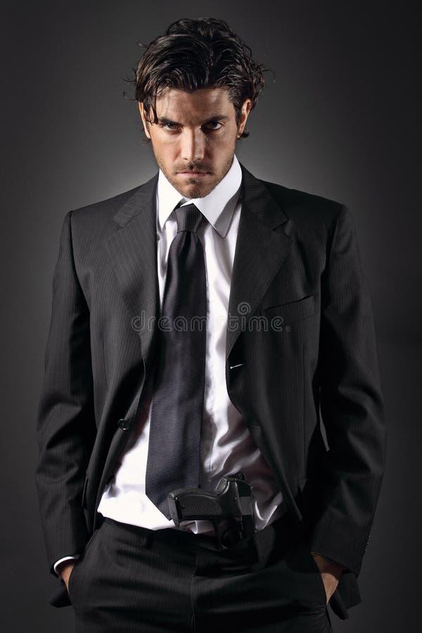Uomo attraente ed elegante che posa con una pistola in suoi pantaloni immagine stock
