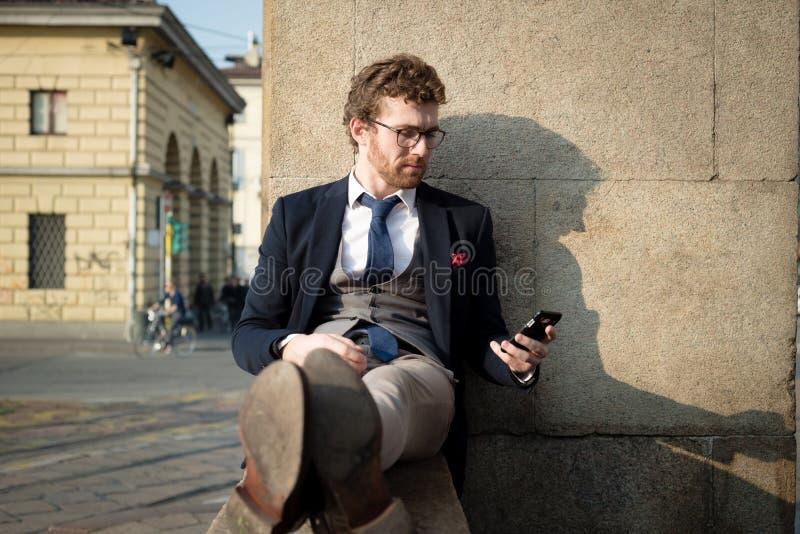 Uomo attraente elegante dei pantaloni a vita bassa di modo sul telefono immagine stock