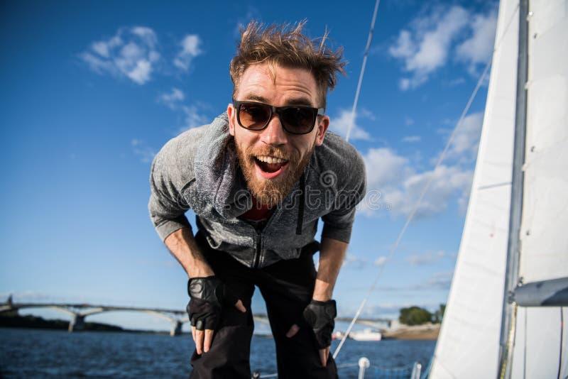 Uomo attraente in occhiali da sole sull'yacht Ritratto vicino di un fronte pazzo felice, risata attraente di yachstman dello spor fotografia stock libera da diritti