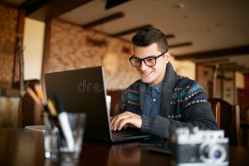 Uomo attraente sorridente dei pantaloni a vita bassa in vetri e maglione di inverno che lavorano al computer portatile in caffè U fotografie stock