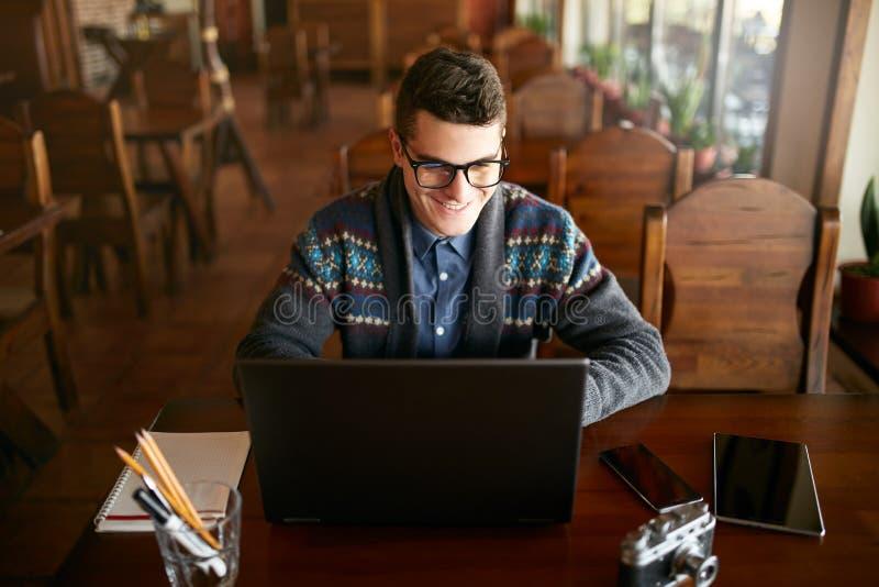 Uomo attraente sorridente dei pantaloni a vita bassa in vetri e maglione di inverno che lavorano al computer portatile in caffè U fotografia stock libera da diritti