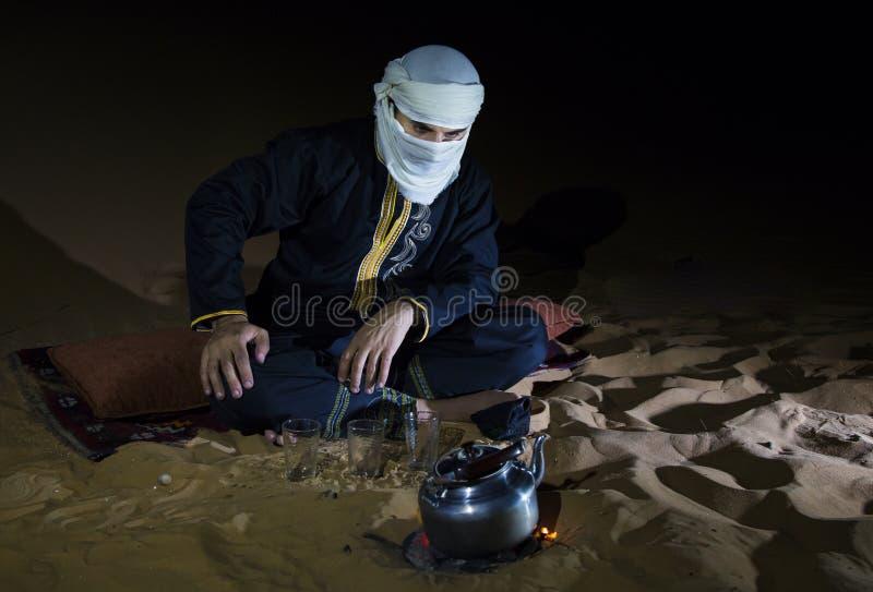Uomo in attrezzatura tradizionale del Tuareg che produce tè in un deserto immagini stock