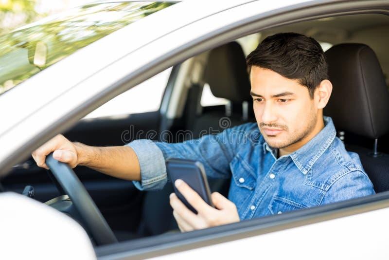 Uomo avventato che conduce automobile e che per mezzo del telefono fotografie stock libere da diritti