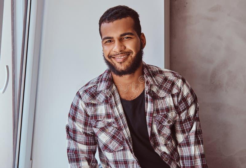 Uomo barbuto afroamericano sorridente che si siede su un davanzale della finestra fotografia stock libera da diritti