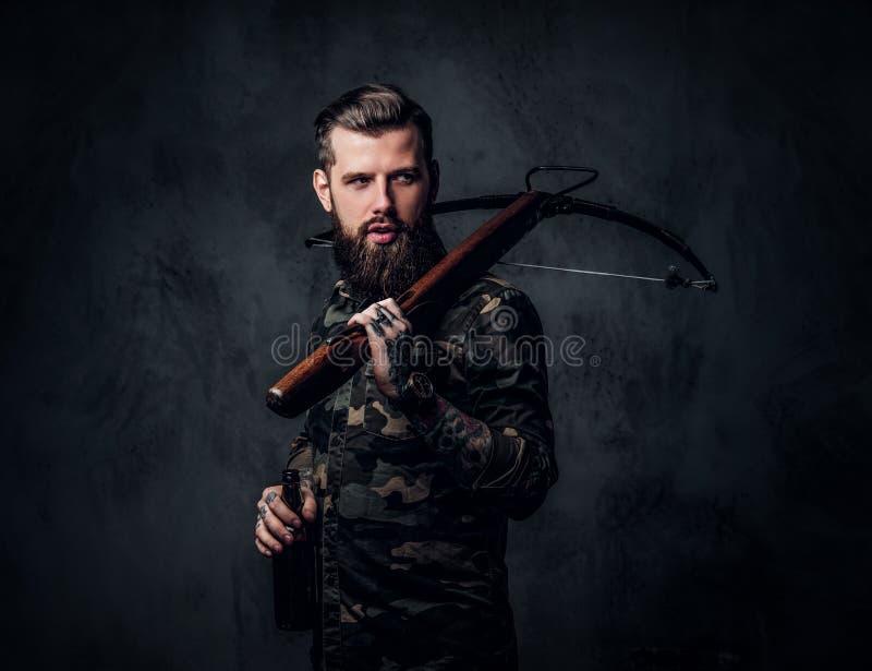 Uomo barbuto alla moda dei pantaloni a vita bassa in camicia militare che tiene una birra del mestiere e una balestra medievale F fotografia stock libera da diritti