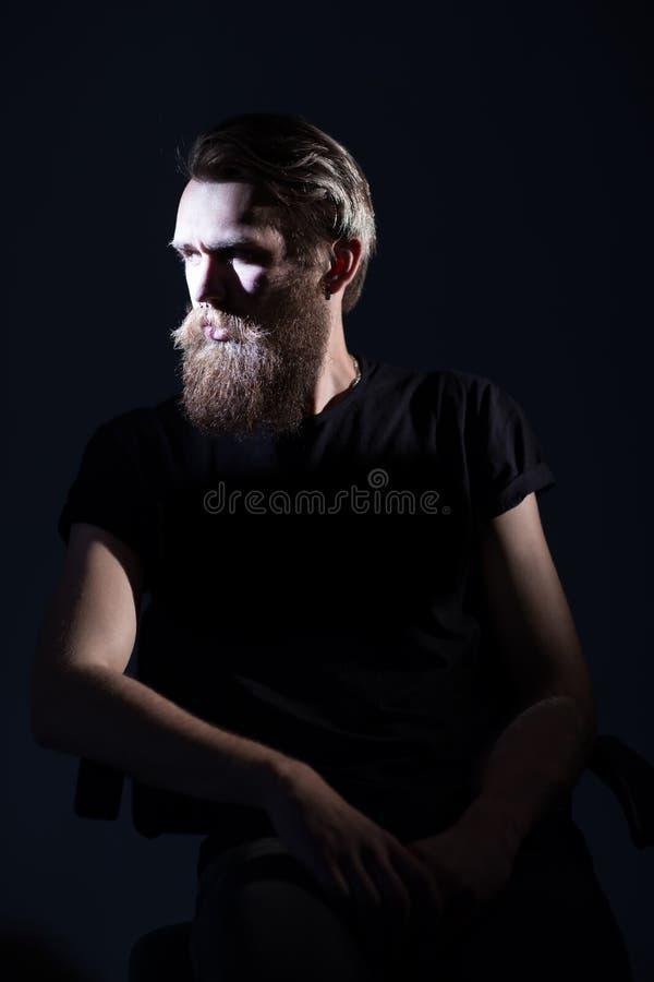 Uomo barbuto alla moda in una maglietta nera che si siede in una sedia immagine stock libera da diritti
