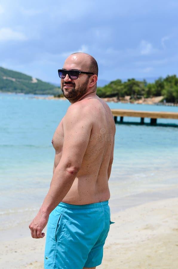 Uomo barbuto alla spiaggia fotografie stock