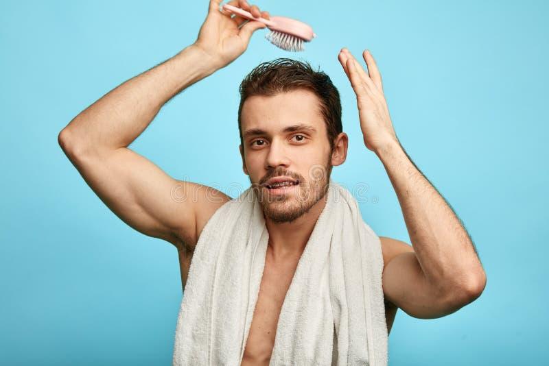 Uomo barbuto attraente che pettina i suoi capelli bagnati immagini stock libere da diritti