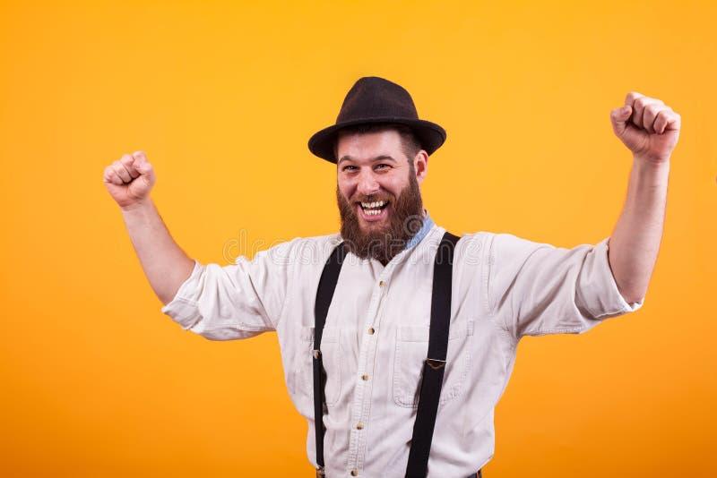 Uomo barbuto attraente che sorride e che indossa un in aumento black hat i suoi pugni sopra fondo giallo fotografie stock