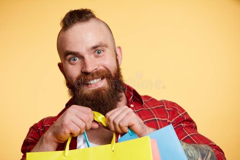 Uomo barbuto, barba lunga Caucasian brutale con i pacchetti di acquisto della tenuta dei baffi fotografie stock
