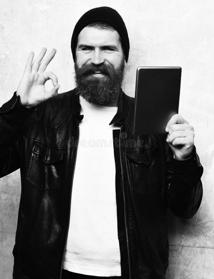 Uomo barbuto, barba lunga Compressa non rasata felice sorridente della tenuta dei pantaloni a vita bassa del caucasian brutale in immagine stock libera da diritti