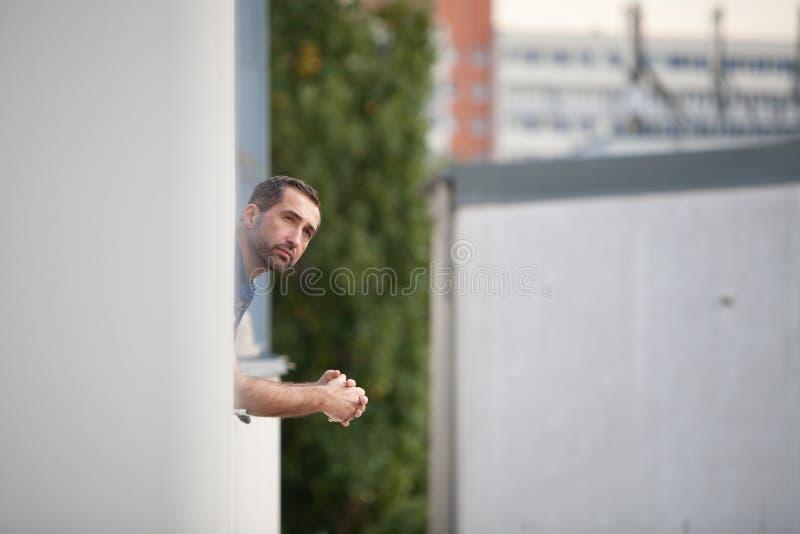 Uomo barbuto bello che guarda dalla finestra che gode della vista immagini stock libere da diritti