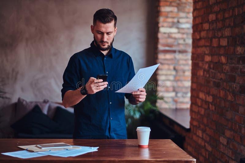 Uomo barbuto bello che per mezzo di uno smartphone e lavorando con i documenti cartacei nell'ufficio con l'interno del sottotetto immagine stock libera da diritti