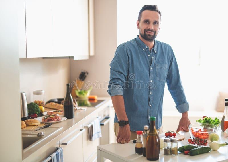 Uomo barbuto bello che posa alla cucina accogliente nei toni bianchi fotografia stock libera da diritti