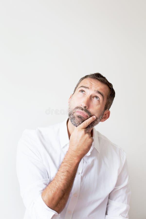 Uomo barbuto bello che sembra curioso fotografia stock libera da diritti