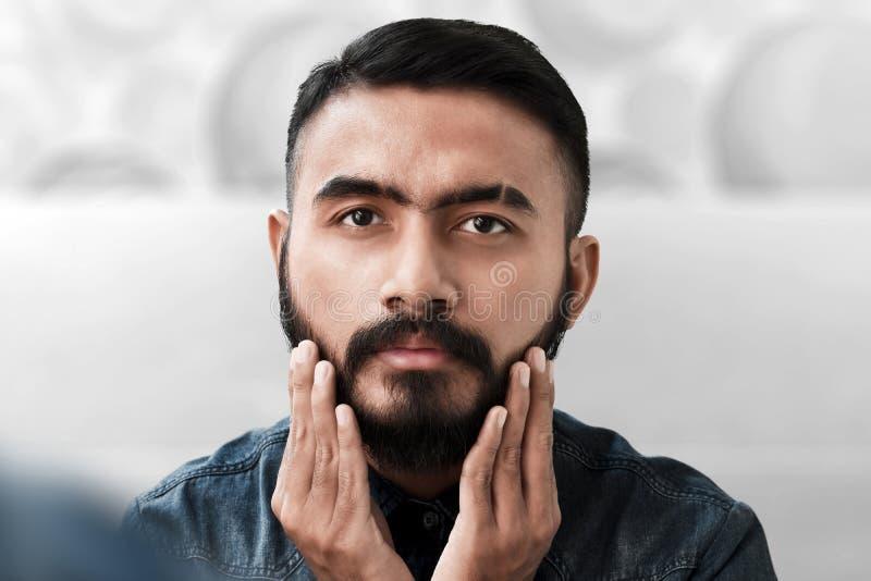 Uomo barbuto bello che tocca la sua barba fotografia stock libera da diritti