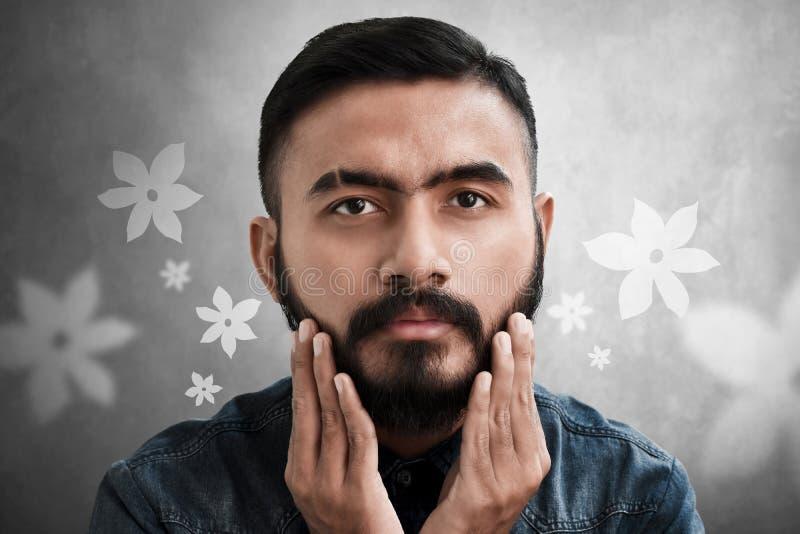 Uomo barbuto bello che tocca la sua barba fotografie stock