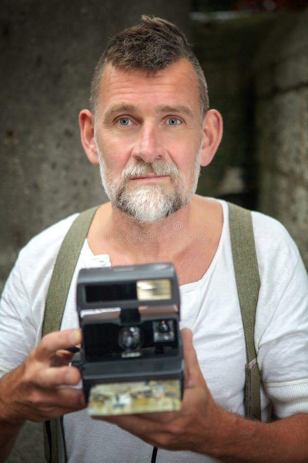 Uomo barbuto bello con la macchina fotografica istantanea immagine stock
