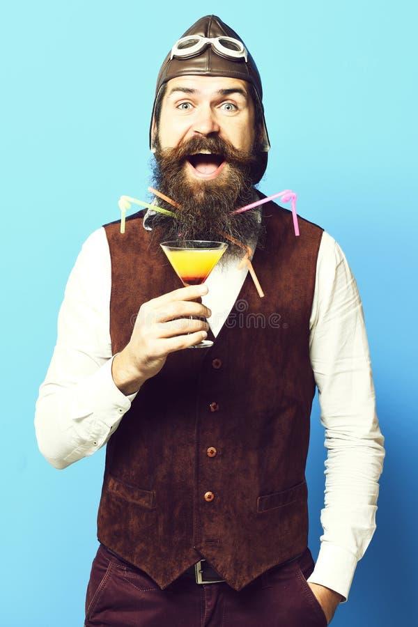 Uomo barbuto bello dell'aviatore o del pilota con la barba lunga e baffi sul fronte felice che tiene vetro della bevanda alcolica immagine stock libera da diritti