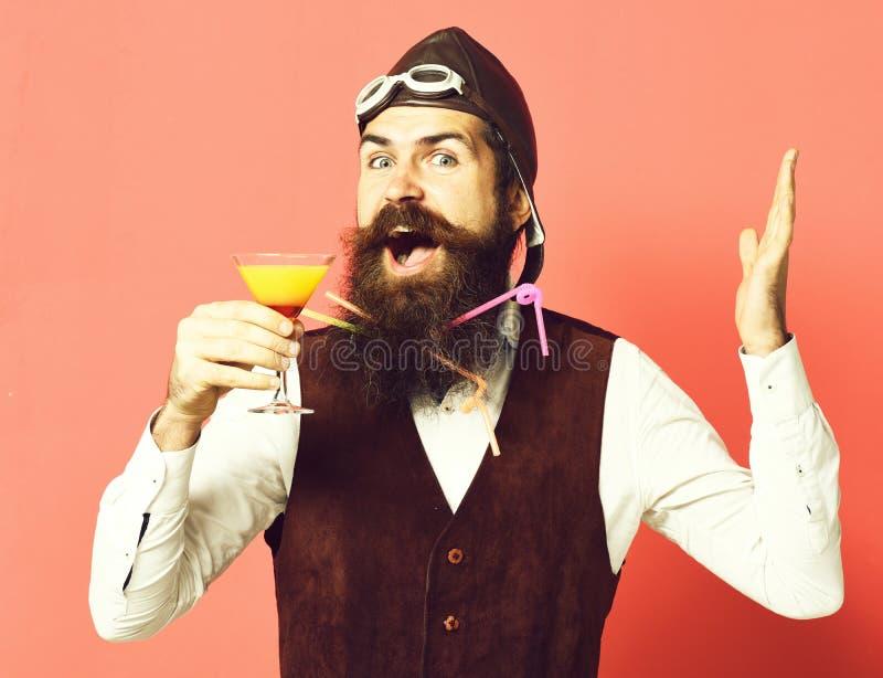 Uomo barbuto bello dell'aviatore o del pilota con la barba lunga e baffi sul fronte felice che tiene vetro della bevanda alcolica immagine stock