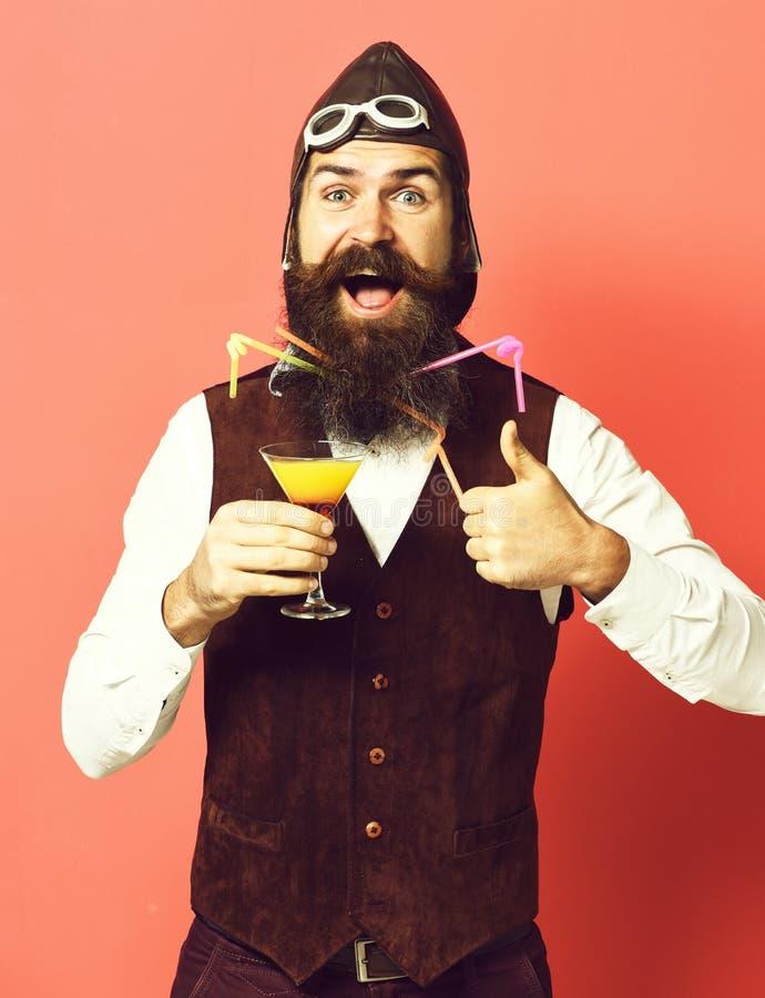 Uomo barbuto bello dell'aviatore o del pilota con la barba lunga e baffi sul fronte felice che tiene vetro della bevanda alcolica fotografia stock libera da diritti