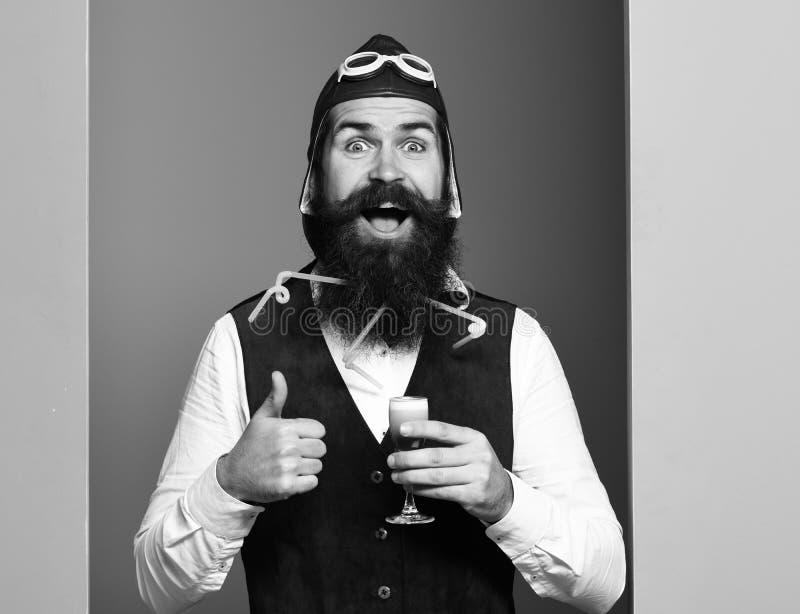 Uomo barbuto bello dell'aviatore o del pilota con la barba lunga e baffi sul fronte sorridente che tiene vetro del colpo alcolico fotografia stock