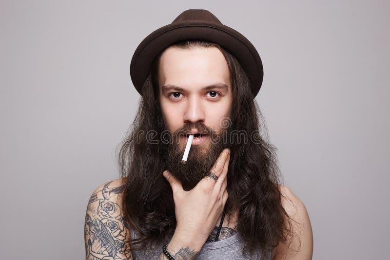 uomo barbuto bello nel cappello che fuma una sigaretta immagine stock libera da diritti