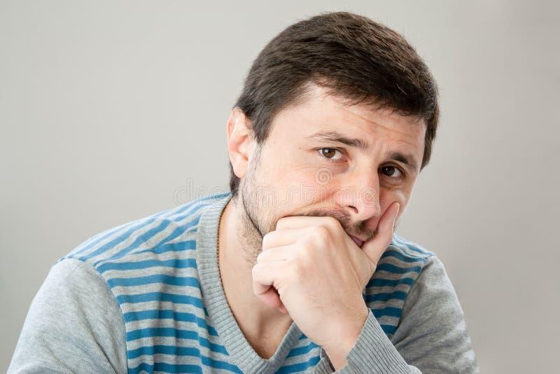 Uomo barbuto bello premuroso in un maglione a strisce che pende la sua testa contro la sua mano che esamina la macchina fotografi immagini stock